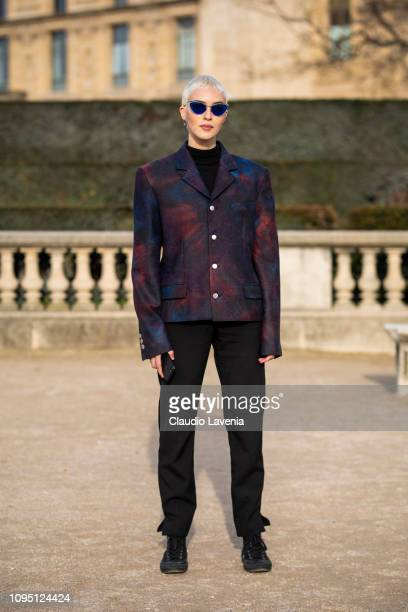 A guest wearing a printed blazer black pants black shoes and blue sunglasses is seen in the streets of Paris before the OffWhite show on January 16...