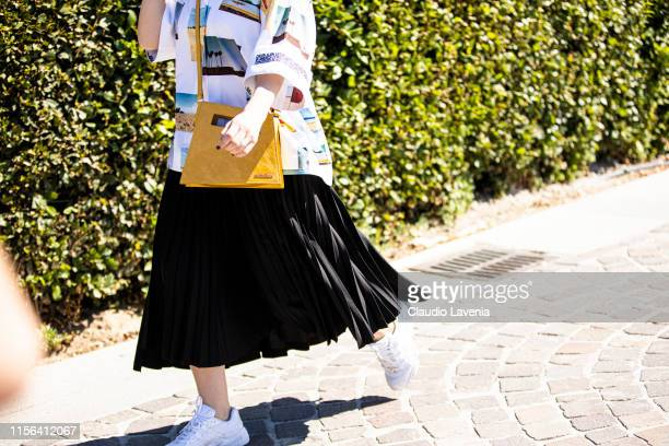 A guest wearing a printed shirt black midi skirt white sneakers and yellow Jacquemus bag is seen during Pitti Immagine Uomo 96 on June 13 2019 in...
