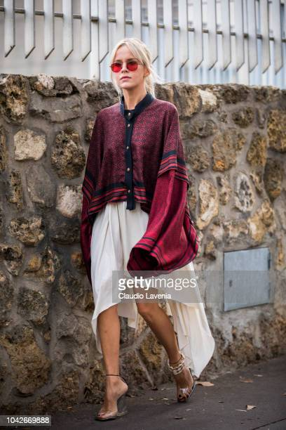 A guest wearing a printed shirt white skirt and seethrough sandals is seen after the Loewe show on September 28 2018 in Paris France