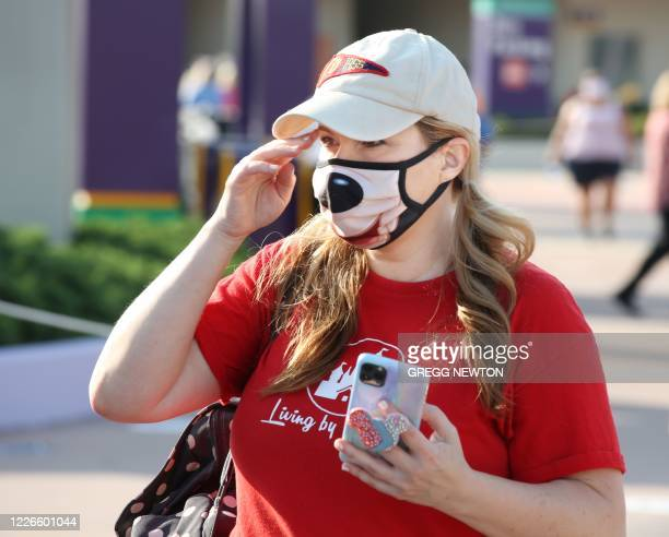 A guest wearing a protective mask arrives at the Magic Kingdom theme park at Walt Disney World on the first day of reopening in Orlando Florida on...