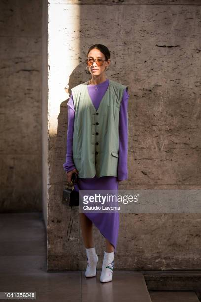 A guest wearing a purple dress a sleeveless green jacket white printed boots and black bag is seen before the Guy Laroche show on September 26 2018...
