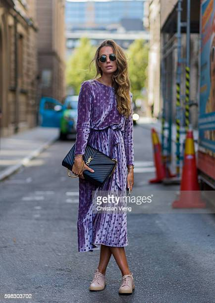 A guest wearing a purple dress and Yves Sain Laurent bag outside Nhorm during the third day of the Stockholm Fashion Week Spring/Summer 2017 on...