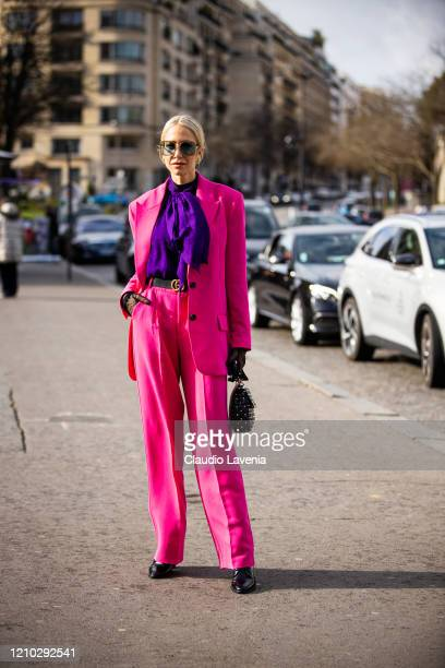 A guest wearing a purple shirt fuchsia suit black sheer gloves and black bag is seen outside Haider Ackermann during Paris Fashion Week Womenswear...