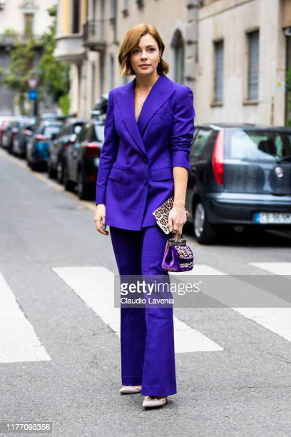 A guest wearing a purple suit and purple decorated bag is seen outside the Dolce e Gabbana show during Milan Fashion Week Spring/Summer 2020 on...