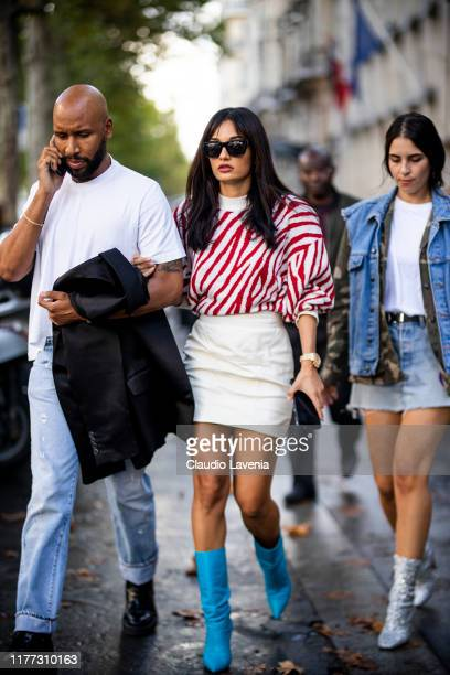 A guest wearing a red and white jumper white mini skirt and light blue boots is seen outside the Faith Connexion show during Paris Fashion Week...