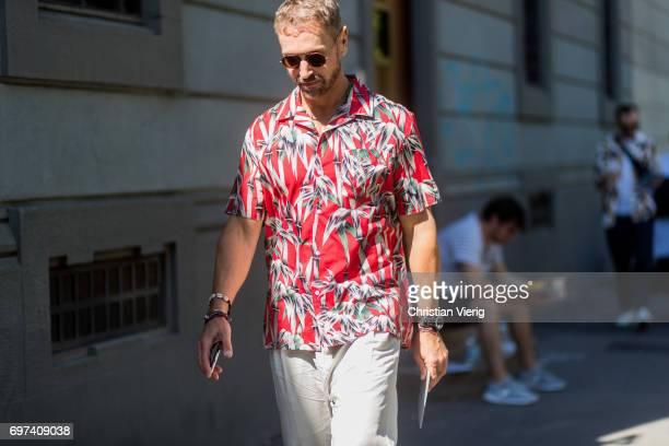 A guest wearing a red button shirt with short sleeves and floral print is seen outside MSGM during Milan Men's Fashion Week Spring/Summer 2018 on...