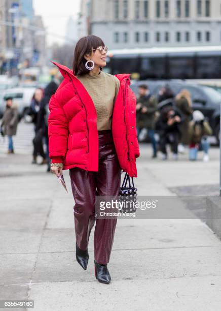 A guest wearing a red down feather jacket outside Michael Kors on February 15 2017 in New York City