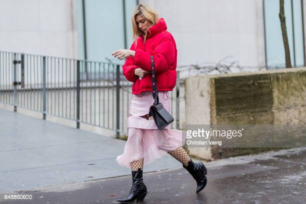 A guest wearing a red down feather jacket pink skirt outside Valentin Yudashkin on March 6 2017 in Paris France