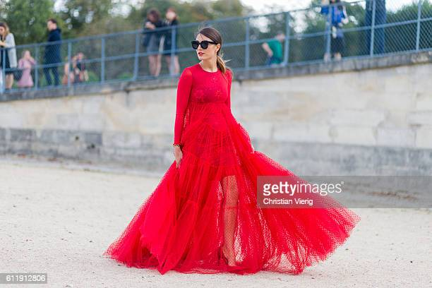 A guest wearing a red dress outside Elie Saab on October 1 2016 in Paris France