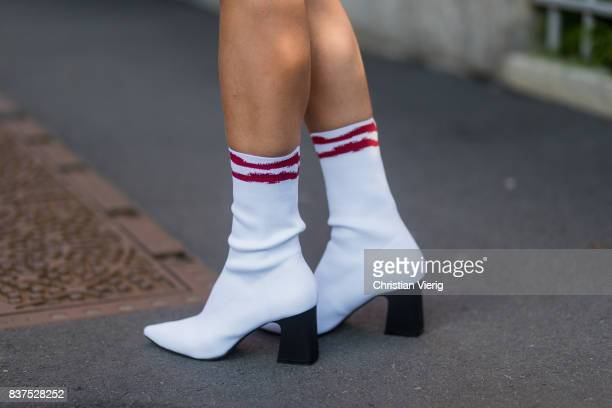 A guest wearing a red dress white sock boots Chanel bag outside Line of Oslo on August 22 2017 in Oslo Norway