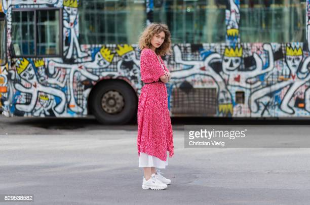 A guest wearing a red dress with dot print outside Ganni on August 10 2017 in Copenhagen Denmark