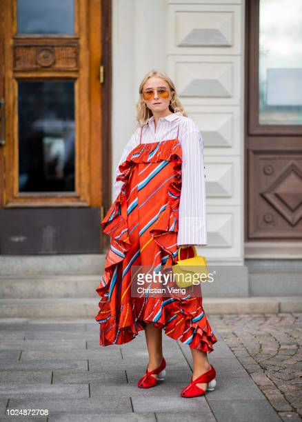 A guest wearing a red dress with stripes yellow mini bag white button shirt is seen during Stockholm Runway SS19 on August 28 2018 in Stockholm Sweden