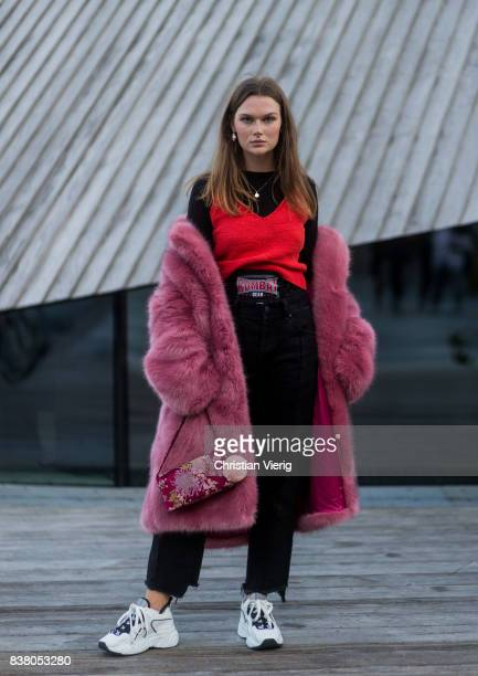 A guest wearing a red fake fur coat boxer shorts black denim jeans sneakers red top outside Mayow on August 23 2017 in Oslo Norway