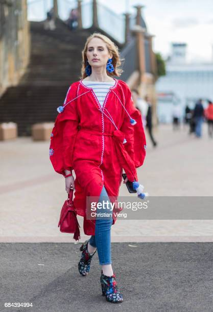 A guest wearing a red jacket denim jeans boots with floral print outside Dyspnea at day 5 during MercedesBenz Fashion Week Resort 18 Collections at...