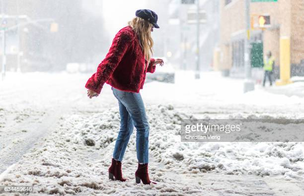 A guest wearing a red jacket flat cap denim jeans outside Desigual on February 9 2017 in New York City