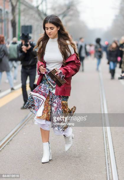 A guest wearing a red jacket skirt white longshirt white boots outside Fendi during Milan Fashion Week Fall/Winter 2017/18 on February 23 2017 in...