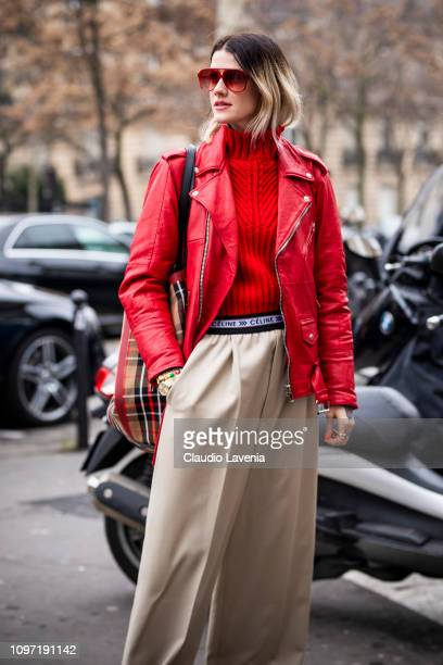 A guest wearing a red jumper red leather jacket beige Celine trousers and checked bag is seen in the streets of Paris before the Acne Femme show on...