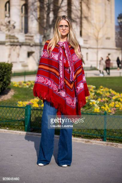 A guest wearing a red mexican poncho is seen in the streets of Paris before the Maison Margiela show during Paris Fashion Week Womenswear Fall/Winter...