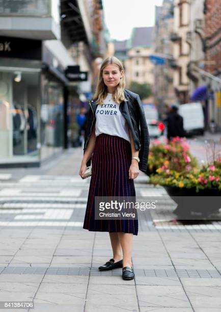 A guest wearing a red midi skirt white tshirt with the print extra power black leather jacket on August 31 2017 in Stockholm Sweden