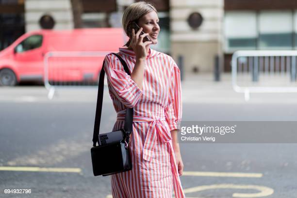 A guest wearing a red striped dress during the London Fashion Week Men's June 2017 collections on June 11 2017 in London England