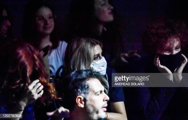 Guest wearing a respiratory mask waits for the start of the Dolce & Gabbana's Women Fall - Winter 2020 fashion collection on February 23, 2020 in...