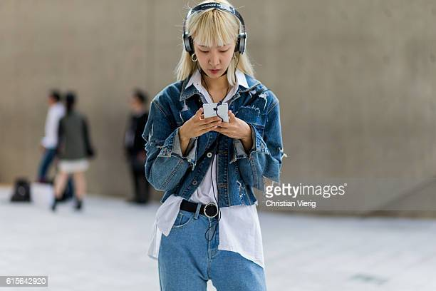 A guest wearing a ripped denim jacket and white button shirt searching for a music song on her phone while listening with her headphones on October...