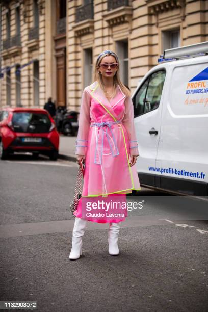 A guest wearing a seethrough coat pink midi dress white boots and pearl bag is seen outside Manish Arora on Day 4 Paris Fashion Week Autumn/Winter...