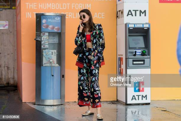 A guest wearing a silk suit with floral print slippers outside Marina Hoermanseder during the MercedesBenz Fashion Week Berlin Spring/Summer 2018 on...