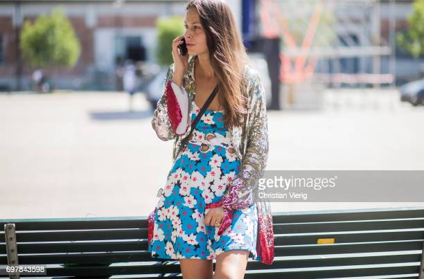 A guest wearing a silver glitter jacket dress with floral print is seen outside GCDS during Milan Men's Fashion Week Spring/Summer 2018 on June 19...