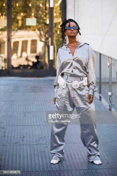 A guest wearing a silver silk blouse matching silk trousers and white fanny pack is seen before the Dries Van Noten show on September 26 2018 in...