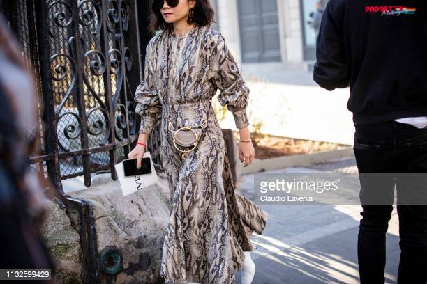 A guest wearing a snake print dress Chloe bag and white boots is seen outside Lanvin on Day 3 Paris Fashion Week Autumn/Winter 2019/20 on February 27...