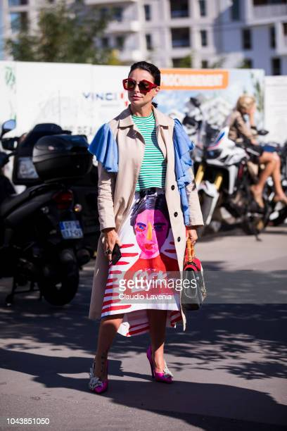 A guest wearing a striped green and white top printed midi skirt beige and blue trench coat colorful bag and pink decorated heels is seen before the...