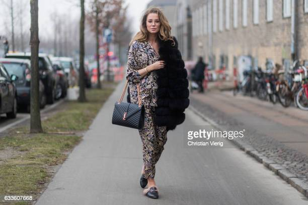 A guest wearing a suit with floral print fur coat YSL bag Gucci loafers outside Munthe during the Copenhagen Fashion Week Autumn/Winter 17 on...