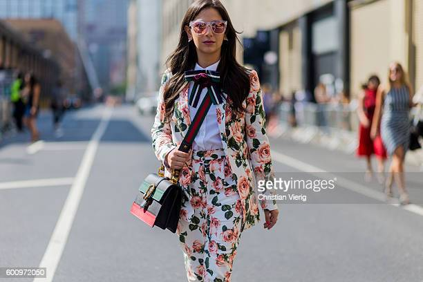 A guest wearing a suit with floral print Gucci bag outside Noon By Noor on September 8 2016 in New York City
