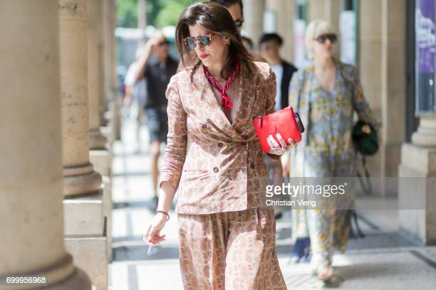 A guest wearing a suit with wide legs red clutch outside Louis Vuitton during Paris Fashion Week Menswear Spring/Summer 2018 on June 22 2017 in Paris...