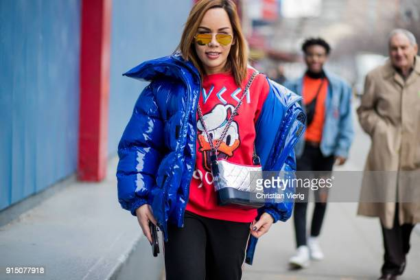 A guest wearing a sweater with Donald Duck print puffer jacket is seen during Mens' New York Fashion Week on February 6 2018 in New York City