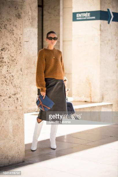 A guest wearing a tan sweater a leather midi skirt white boots and Loewe bag is seen after the Marques Almeida show on September 26 2018 in Paris...