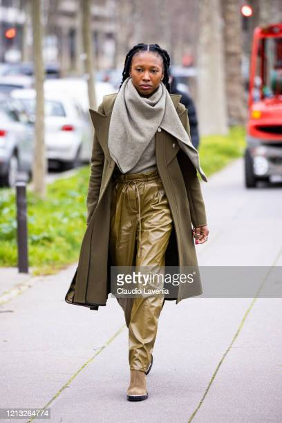 Guest, wearing a taupe sweater, green leather pants, military green coat and beige boots, is seen outside Loewe, during Paris Fashion Week -...