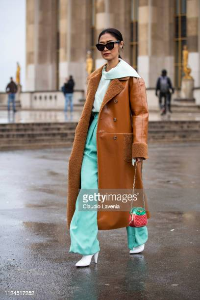 A guest wearing a teal top teal trousers white boots green and red Gucci bag and long beige leather jacket is seen outside Elie Saab show during...
