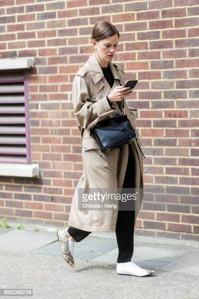 A guest wearing a trench coat and Loewe bag during the London Fashion Week Men's June 2017 collections on June 12 2017 in London England