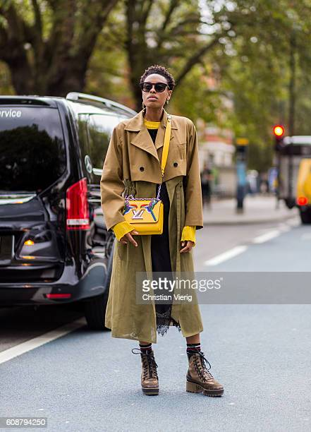 A guest wearing a trench coat and yellow Louis Vuitton bag outside Christopher Kane during London Fashion Week Spring/Summer collections 2017 on...