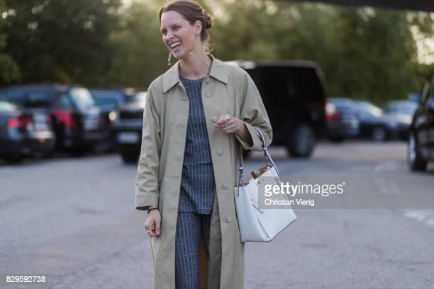 A guest wearing a trench coat outside Saks Potts on August 10 2017 in Copenhagen Denmark