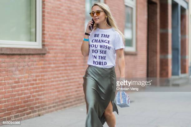 A guest wearing a tshirt with the print be the change you wish to see the world seen in the streets of Manhattan outside Tibi during New York Fashion...