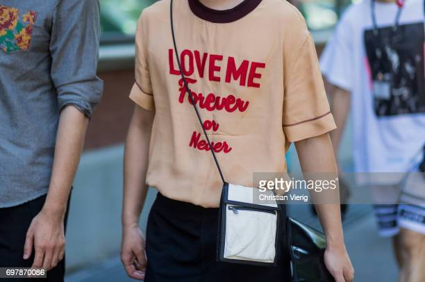 A guest wearing a tshirt with the print Love me forever or never is seen outside Fendi during Milan Men's Fashion Week Spring/Summer 2018 on June 19...