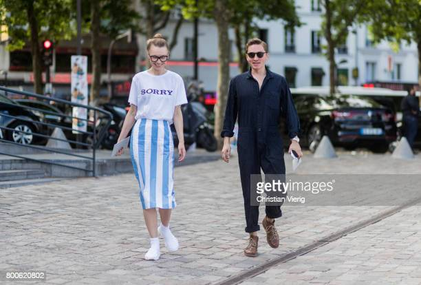 A guest wearing a tshirt with the print Sorry blue white striped skirt and a guest wearing a navy jumpsuit outside Sacai during Paris Fashion Week...