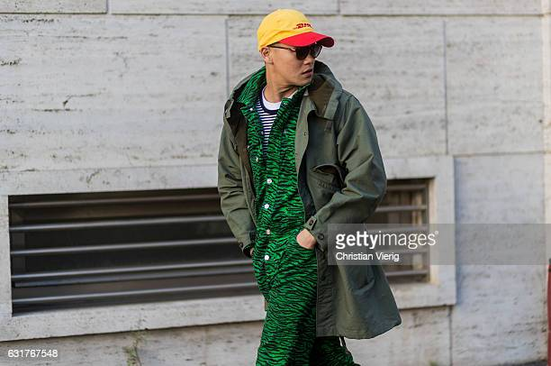 A guest wearing a Vetements cap jumpsuit green parka during Milan Men's Fashion Week Fall/Winter 2017/18 at Salvatore Ferragamo on January 15 2017 in...