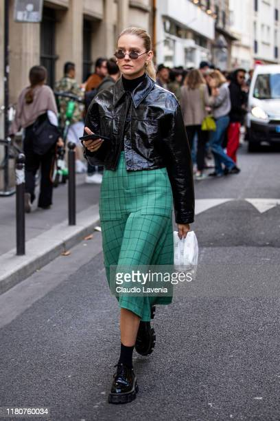 Guest, wearing a vinyl black jacket, green checked midi skirt and black shoes, is seen outside the APC show during Paris Fashion Week - Womenswear...