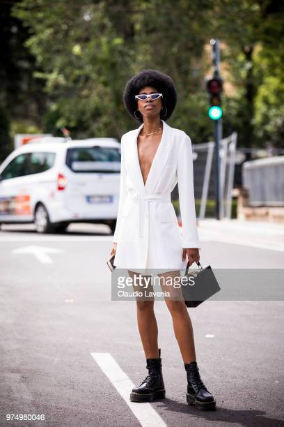 A guest wearing a white blazer and combat boots is seen during the 94th Pitti Immagine Uomo at Fortezza Da Basso on June 14 2018 in Florence Italy