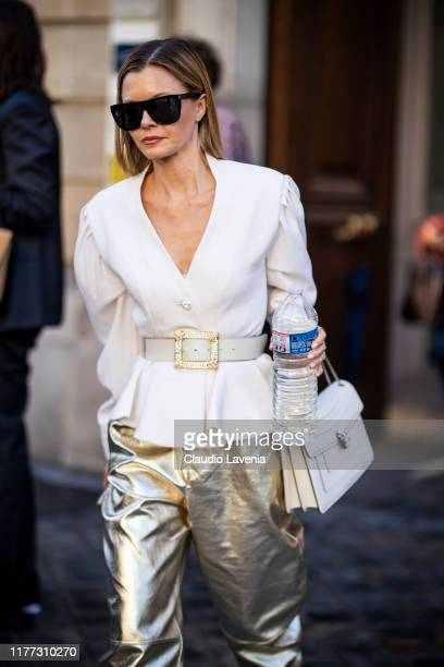 A guest wearing a white blazer gold pants and white Bulgari bag is seen outside the Faith Connexion show during Paris Fashion Week Womenswear Spring...