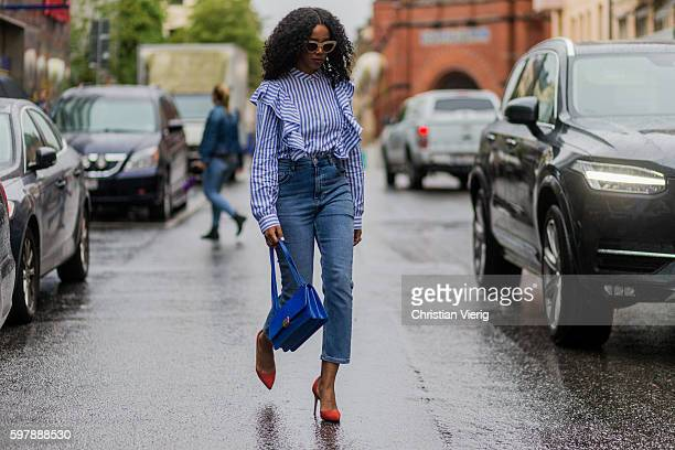 A guest wearing a white blue striped shirt blue bag orange heels and blue high waisted denim jeans outside Busnel during the first day of the...